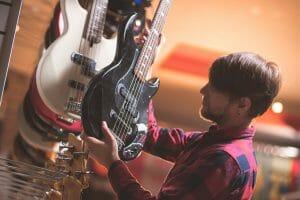 Man choosing an electric bass guitar