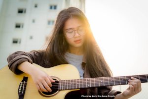 Picture of girl practicing her acoustic guitar outside